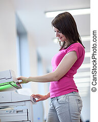 pretty young woman using a copy machine (shallow DOF; color toned image)