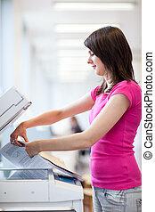 Pretty, young woman using a copy machine