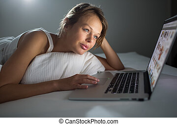 Pretty, young woman using her laptop computer in bed