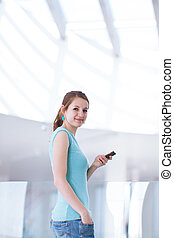 Pretty, young woman using her mobile phone/speaking on the phone in a public area (shallow DOF; color toned image)