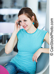 Pretty young woman using her mobile phone/speaking on the phone in a public area (shallow DOF; color toned image)