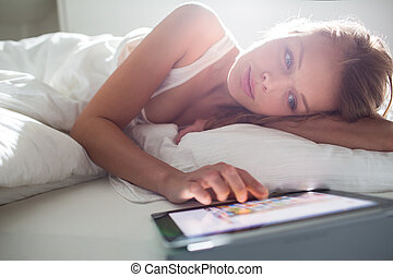 Pretty, young woman using her tablet computer in bed