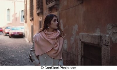Pretty young woman walking alone through the alley. Girl going in the side street and thinking, looking around.