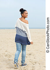 pretty young woman walking on the beach and looking over shoulder