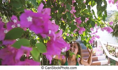 Pretty young woman walks through a bunch of pink flowers and smiles, slow motion.
