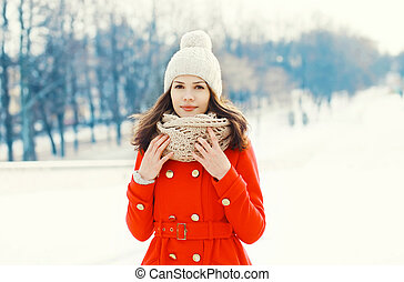 Pretty young woman wearing a red coat, knitted hat and scarf in winter day