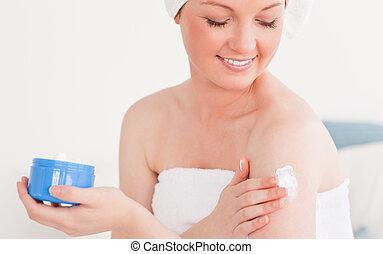 Pretty young woman wearing a towel using skin cream