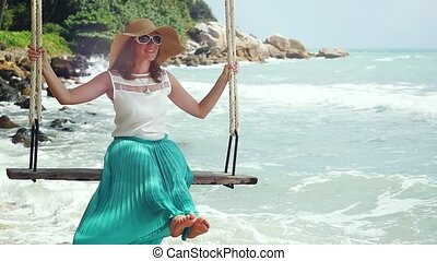 Pretty young woman wearing hat and sunglasses relaxes on the swing at stony beach in slow motion with beautiful sun flare effect. 1920x1080