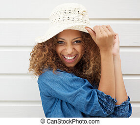 Pretty young woman wearing summer hat and laughing