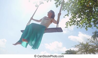 Pretty young woman wearing sunglasses relaxes on the swing...