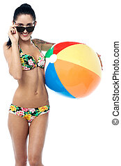 Pretty young woman with a beach ball