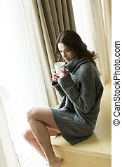 Pretty young woman with cup of coffee by the window