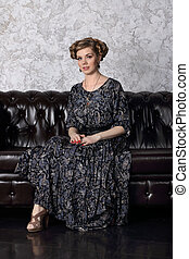 Pretty young woman with hairdo and in dress sits on sofa in studio
