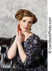 Pretty young woman with hairdo and makeup poses on sofa in studio