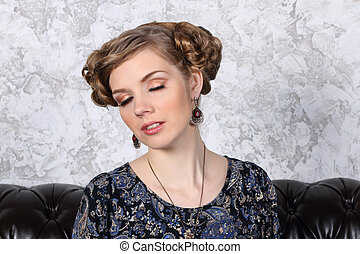 Pretty young woman with hairdo poses with closing eyes on sofa in studio
