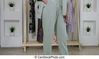 woman with long fair hair wears mint pantsuit and poses -...