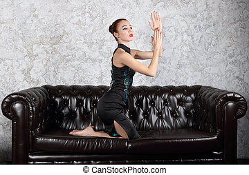 Pretty young woman with makeup poses as geisha on black leather sofa in studio