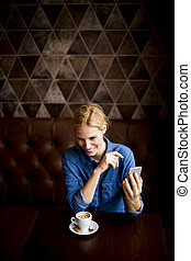 Pretty young woman with mobile phone in the cafe