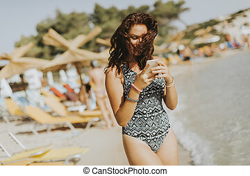 Pretty young woman with mobile phone on the beach