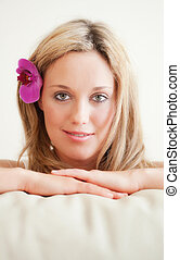 Pretty young woman with orchid in the hair