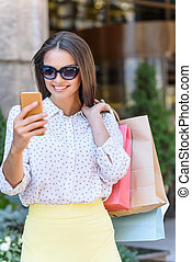 Pretty young woman with phone and packets