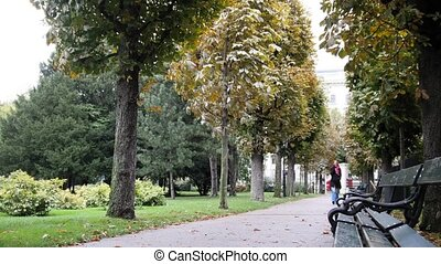 Pretty young woman with red hair and glasses walking in park...