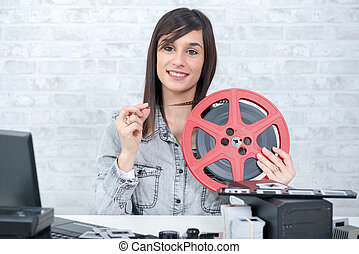 pretty young woman with reel 16mm film