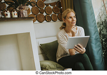 Pretty young woman with tablet in the cafe