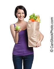 Pretty young woman with the packet full of healthy nutrition, isolated, white background