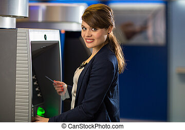 Pretty, young woman withdrawing money from her credit card...