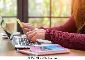 Pretty Young womans hands holding a credit card and using laptop computer for online shopping. Online payment. Female working on laptop in a cafe. Note book, pen and credit card put on table.