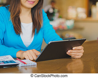 Pretty Young womans hands holding and using tablet for...