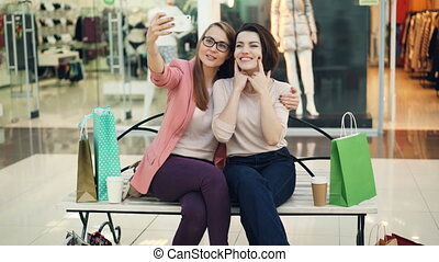 Pretty young women are taking selfie using smartphone camera sitting on bench in shopping mall and having fun. Modern technology, shops and friends concept.