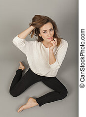 pretty young women posing in siting position with hands on her face and hair