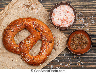 Pretzel with caraway seeds and coarse salt on a dark wooden table. Selective focus. Top view