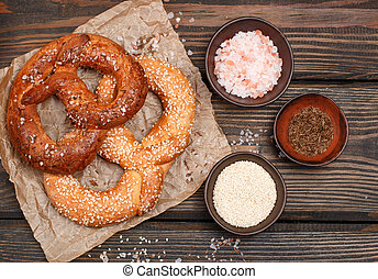 Pretzel with caraway seeds, sesame seeds and coarse salt on a dark wooden table. Selective focus. Top view