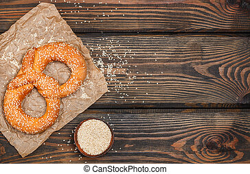 Pretzel with sesame seeds on the dark wooden table. Selective focus. Copy space. Top view