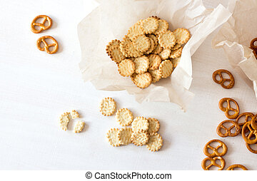 Pretzels and crackers on wooden table from above.