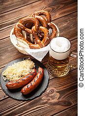 Pretzels, bratwurst and sauerkraut on wooden table -...