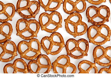 Pretzels lay on a tabletop on white table