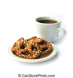 Pretzels with sesame seeds on a plate and cup of coffee on white background