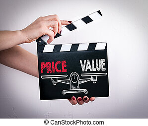 Price and Value balance. Female hands holding movie clapper