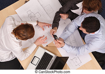 Architect showing couple of clients blueprints in the office. Aerial shot taken from directly above the table