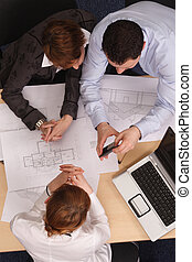 Three business people calculating a cost - blueprints in background