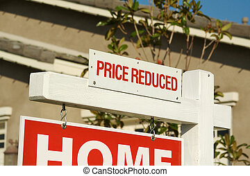 Price Reduced Real Estate Sign in Front of Beautiful New Home.