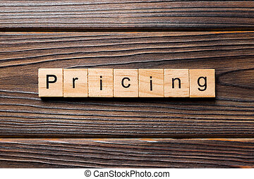 Pricing word written on wood block. Pricing text on table, concept