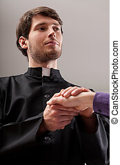Young christian priest is holding believer hand