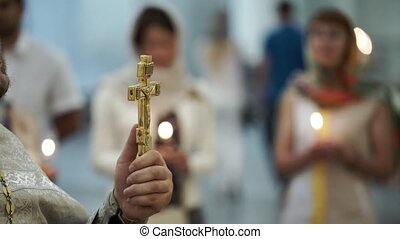Priest in church praying with cross
