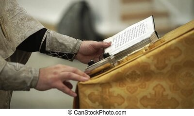 Priest in church praying with a book