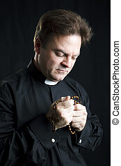 Priest in Prayer - Priest holding his rosary and praying....